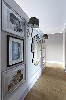 aranżacja ściany ze zdjęciami w ramkach, lustrem i kinkietem